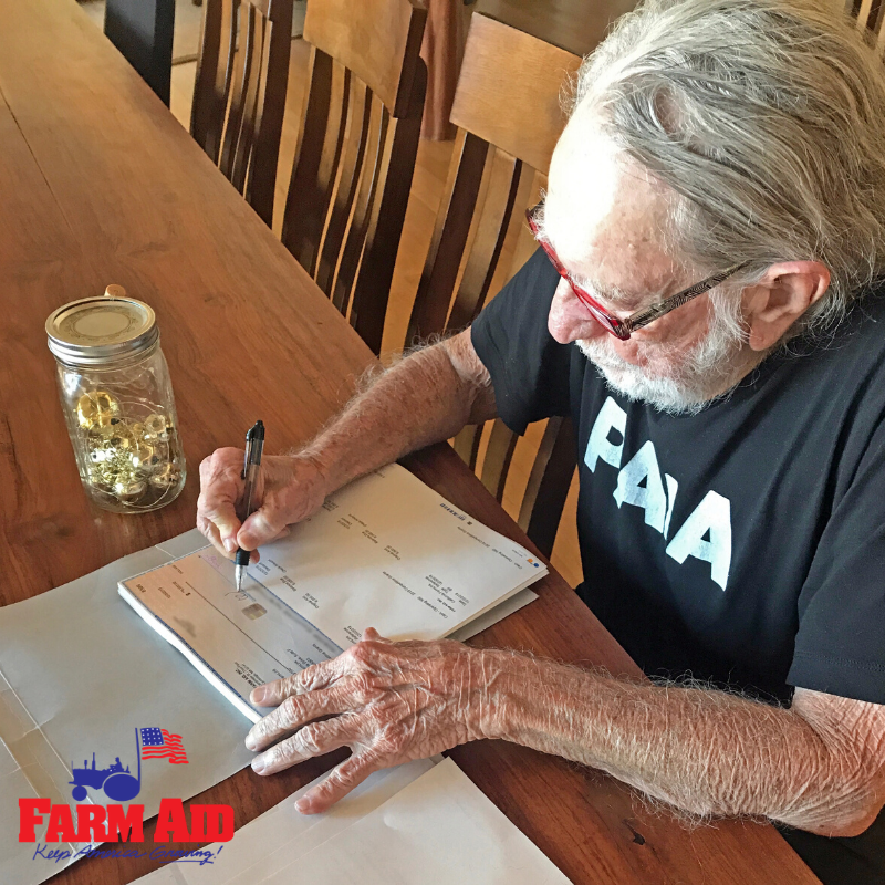 Willie Nelson signing Farm Aid grant checks